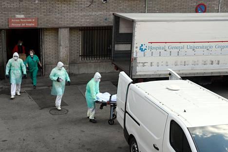 Sairaanhoidon ammattilaiset kuljettivat ruumista madridilaisen sairaalan edustalla maaliskuun 25. päivänä. Espanjassa on Italian jälkeen todettu eniten koronaviruksesta johtuvia kuolemantapauksia maailmassa.