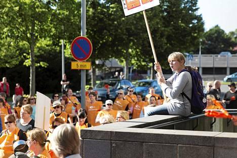Janika Leach protestoi kyltin kanssa JHL:n järjestämässä mielenilmauksessa Espoon kaupunginvaltuuston kokouksen alla maanantaina.