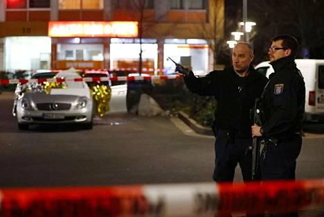 Poliiseja toisen iskupaikan lähistöllä torstain vastaisena yönä. Ampumisia tapahtui taustalla näkyvässä rakennuksessa sijainneessa kahvila-kioskissa ja sen edustan parkkipaikalla.