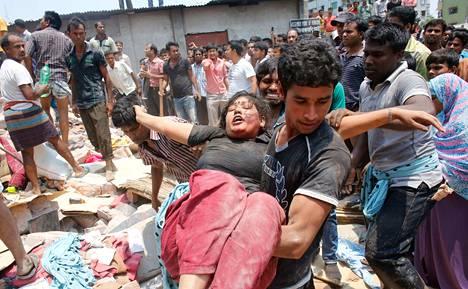 Romahtaneesta rakennuksesta pelastettua naista kannettiin turvaan keskiviikkona Savarissa Bangladeshissa.