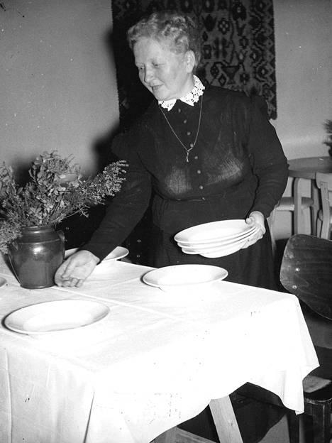 Kekrijuhlien emäntä, rouva Ester Mömmö kattamassa pitopöytää. Isännän paikka kuuluu monien urheilumaaottelujen kapteenille, metsäteknikko Oiva Halmetojalle.