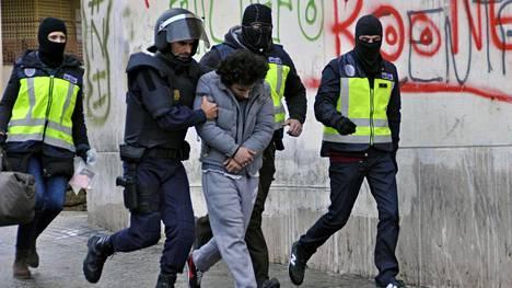 Poliisi talutti jihadistiryhmään kuulumisesta epäiltyä miestä Espanjalle kuuluvassa Melillan kaupungissa Marokon rannikolla maaliskuussa 2014.