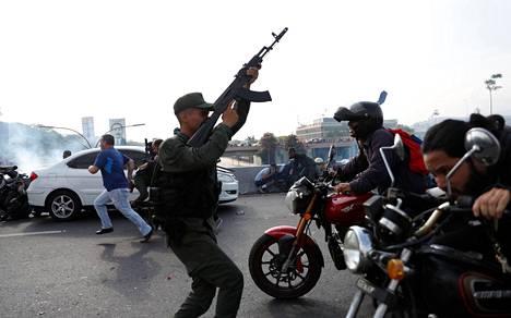 Sotilas ja paikalliset reagoivat lähellä kuuluviin laukauksiin Caracasin lentokentän lähellä Venezuelassa.
