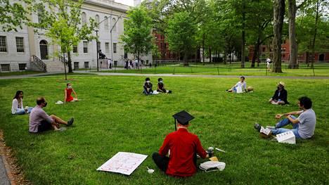 Joukko nuoria juhlisti turvavälejä pitäen valmistujaisia toukokuussa Harvardin yliopiston oikeustieteen kampuksen edessä Massachusettsin osavaltiossa.
