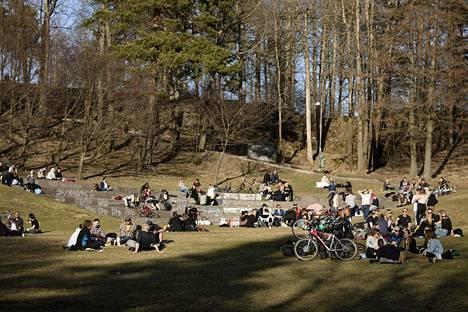 Ihmiset nauttivat lämpimästä kevätsäästä Alppipuistossa Helsingissä lauantaina.