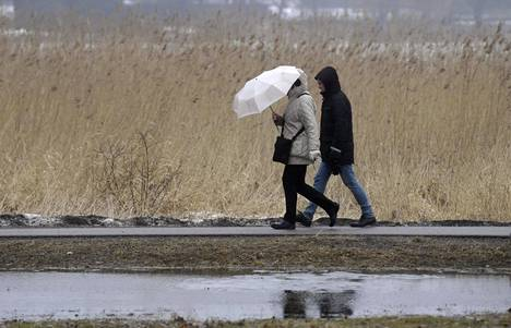 Ulkoilijoita Töölönlahden rannalla Helsingissä vesisateessa 29. maaliskuuta 2021. Sateita on odotettavissa jälleen tulevana viikonloppuna.