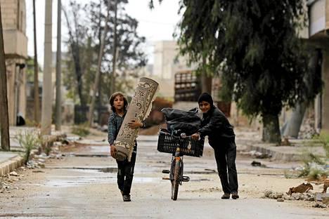 Pojat kantoivat mattoa ja taluttivat polkupyörää Syyrian sodan autioittamalla kadulla Aleppossa.