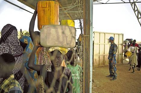 Pakolaiset kantoivat vettä pakolaisleiriksi muutettuun YK-tukikohtaan Malakalissa Etelä-Sudanissa helmikuussa. Leirissä puhkesi tiistaina taistelu, jossa kuoli kymmenen ihmistä.