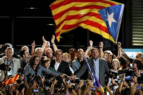Katalonian itsehallintoalueen presidentti Artur Mas (keskellä) kätteli itsenäisyysmielisten ehdokkaita voitonjuhlissa Barcelonassa sunnuntai-iltana.