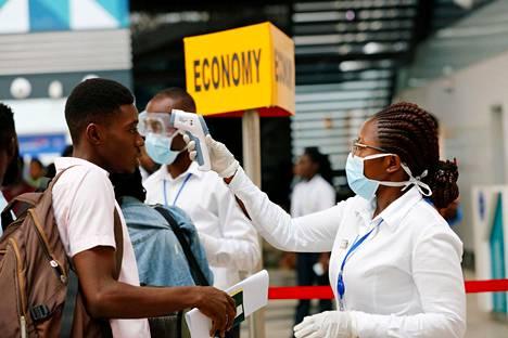Terveydenhuollon työntekijä mittasi matkustajan ruumiinlämmön Kotokan lentokentällä Ghanassa torstaina.