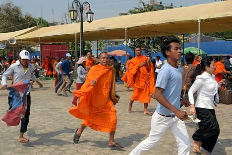 Buddhalaiset munkit ja mielenosoittajat juoksevat pakoon kilvin ja pampuin varustautuneita turvallisuusjoukkoja Demokratia-puistossa  Phnom Penhissä lauantaina.