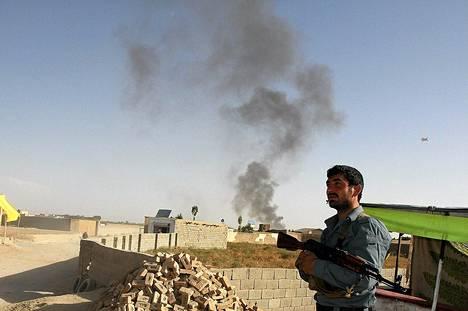 Afganistanilainen poliisi vartioi Talebanin iskun jäljiltä savuavaa kansainvälistä tukikohtaa Ghanzin maakunnassa keskiviikkona.