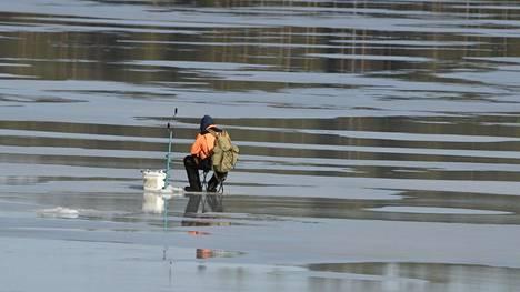 Mies pilkillä järven jäällä Pieksämäellä 18. maaliskuuta 2020.