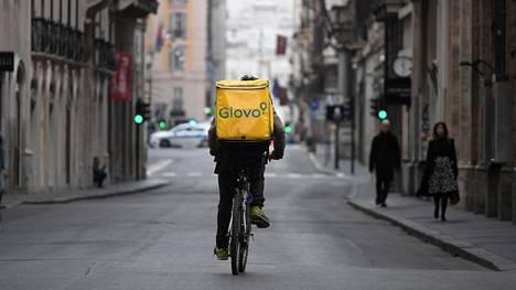 Ruokalähetti pyöräili hiljentyneessä Rooman keskustassa 14. maaliskuuta.