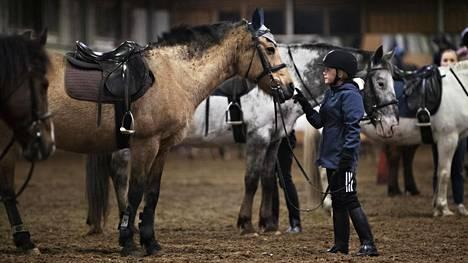 Ella Mäkinen, 10, taputti Dana-ponia ratsastustunnin jälkeen Husön ratsastuskeskuksen maneesissa.