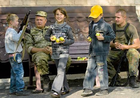 Poika piteli asetta ukrainalaisen sotilaan valvonnassa Soledarin kaupungissa lähellä Donetskia. Noin 70 Venäjän armeijan sotilasta on Itä-Ukrainassa tapaamassa Ukrainan armeijan sotilaita ja kapinallisia neuvotellakseen tulitauon säännöistä alueella.