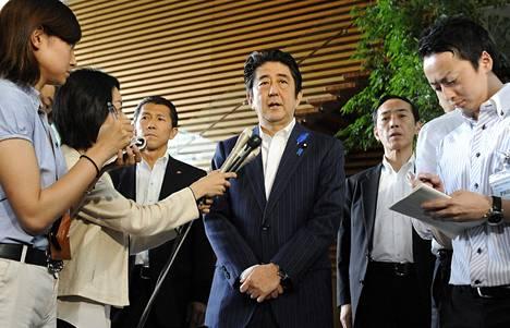 Japanin pääministeri Shinzo Abe (kesk.) kertoi torstaina maan höllentävän joitakin Pohjois-Koreaan kohdistuvia pakotteita.