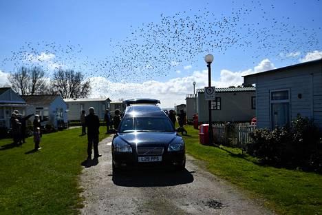 Hautajaisvieraita covid-19-tautiin kuolleen vainajan muistotilaisuudessa Sheppeyn saarella sijaitsevassa Leysdown-on-Sean karavaanimökkikylässä 19. maaliskuuta.