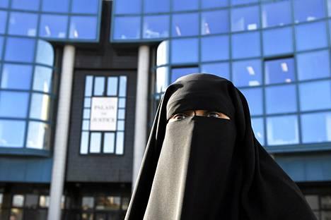 Hind Ahmas on pukeutunut niqab-huiviin, kiellosta huolimatta, oikeustalon ulkopuolella Pariisissa torstaina.