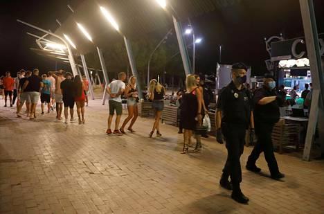 Poliisit kiertävät maskit kasvoillaan Punta Ballenan baarikatua ja valvovat järjestystä.