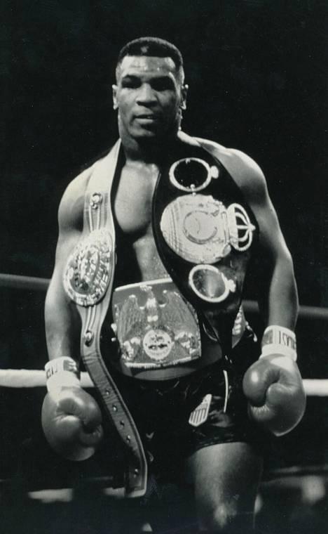 Mike Tyson kolmen mestaruusvyön kanssa vuonna 1988.