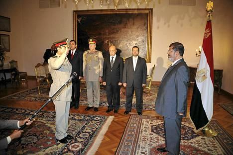 Abdel-Fattah el-Sissi tervehti presidentti Mursia lauantaina presidentinlinnassa.