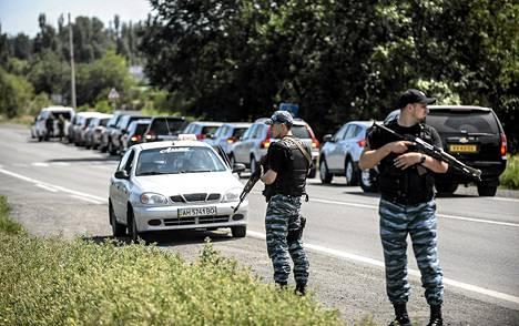 Venäjän-mieliset joukot vartioivat tutkijoiden reittiä MH17 -lennon tuhoaluetta kohti Donetskissa maanantaina 28. heinäkuuta.