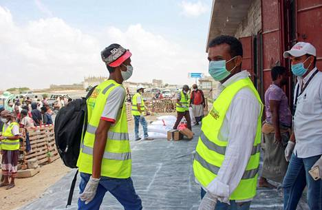 Hengityssuojaimia käyttäneet YK:n ruokaohjelman WFP:n työntekijät jakoivat hätäapua kodeistaan paenneille jemeniläisille pääkaupungissa Sanaassa lauantaina.