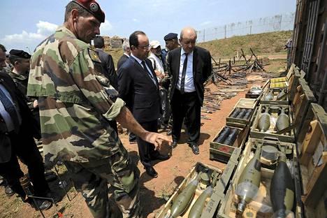 Ranskan presidentti Francois Hollande (keskellä) ja puolustusministeri Jean-Yves Le Drian (oik.) tarkastelivat kapinallisilta takavarikoituja aseita Keski-Afrikan Banguissa helmikuun lopulla.
