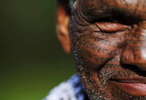 Hindin kielellä kirjoitettu jumala Raman nimi toistuu lukemattomia kertoja Tiharu Ramin, 70, kasvoissa.