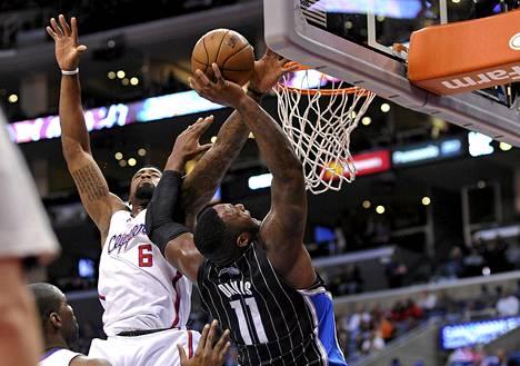 LA Clippersin DeAndre Jordan (vas.) torjuu Orlandon Glen Davisin heiton maanantain NBA-pelin alkuneljänneksellä.