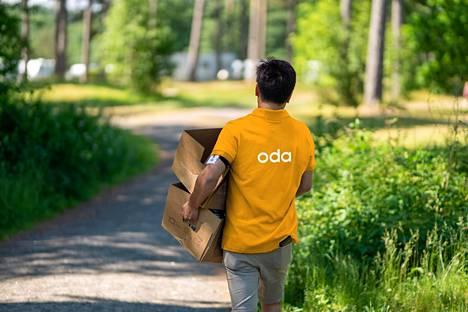Mainoskuva Odan kuljetuksista. Mies kantaa laatikoita Oda-logopaidassa.