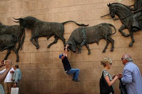 Turisti poseeraa kuvaajalle härkäveistoksen sarvista roikkuen Las Ventasin härkätaisteluareenalla Madridissa tiistaina.
