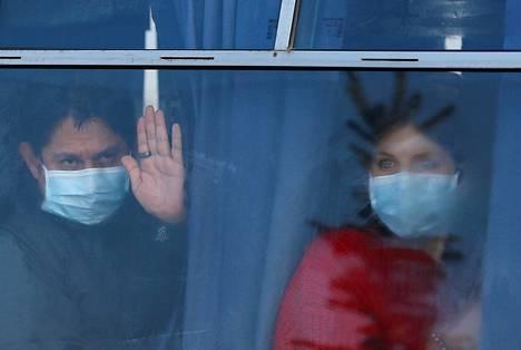 Kiinasta evakuoidut ihmiset katselivat bussin ikkunasta Harkovan lentoasemalla, jonne heidät oli tuotu Wuhanista lennoilla Kiovan kautta.