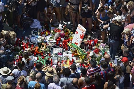 Ihmiset kerääntyivät perjantaina Barcelonan La Ramblalle jättämään kukkia, kynttilöitä ja muita esineitä terrori-iskun uhrien muistolle.