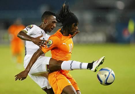 Ghanan Harrison Afful (vas.) ja Norsunluurannikon Gervinho taistelivat pallosta Batassa pelatussa Afrikan mestaruusturnauksen loppuottelussa.