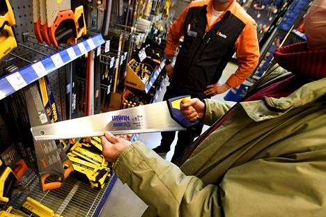 Myyjä esittelee sahaa Ruoholahden K-Raudassa Helsingissä 5. helmikuuta 2021. Rautakaupat pysyvät auki myös mahdollisten liikkumisrajoitusten aikana.