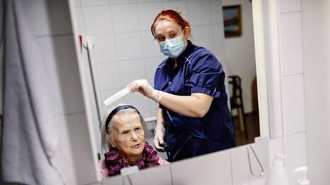 Lähihoitaja Pipsa Lehtimäki auttaa Ann-Mari Johanssonia aamutoimissa Attendon hoivakoti Jaspiksessa Vantaalla.