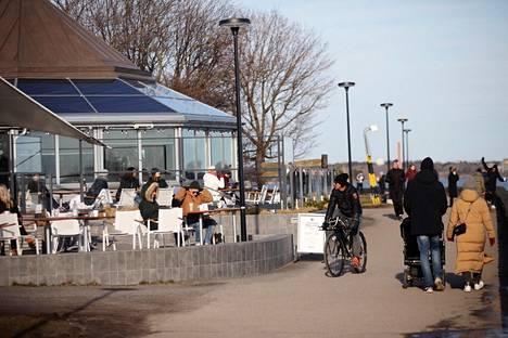 Ulkoilijoita terassilla ja Kaivopuiston rannassa Helsingissä 22. maaliskuuta.