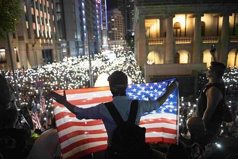 Mielenosoittaja levitti Yhdysvaltain lipun Hongkongin demokratialiikkeen mielenosoituksessa lokakuussa 2019.