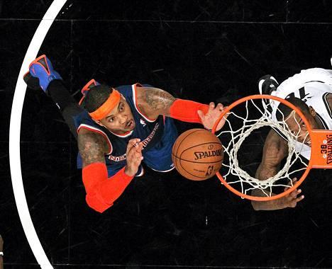 New York Knicksin Carmelo Anthony nappaa levypallon ottelussa Brooklyn Netsiä vastaan torstaina.