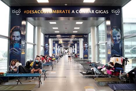 Matkustajia makaili tiistaina tilapäisillä sängyillä Kolumbian pääkaupungin Bogotan El Doradon lentokentällä, joka suljettiin koronaviruksen vuoksi tiistaina.