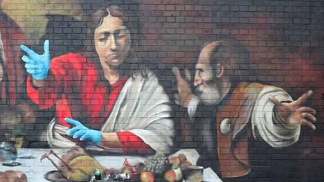 Brittiläinen katutaiteilija Lionel Stanhope viimeisteli Lontoossa versiota Caravaggion Emmauksen ateriasta. Tällä kertaa Jeesukselle on lisätty suojakäsineet.