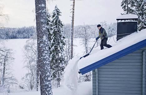 Mikkelin Tikkalassa mökkitalkkari Mika Venemies pudottaa lunta mökin katolta.