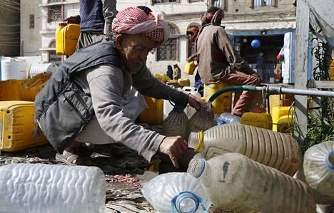 Jemeniläiset täyttävät kanistereita vedellä maanantaina pääkaupunki Sanaassa. Jemenin sota on YK:n mukaan maailman pahin humanitaarinen kriisi.