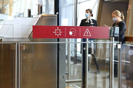 Kyltti muistutti koronavirustoimenpiteistä Helsinki-Vantaan lentokentällä toukokuussa 2021.
