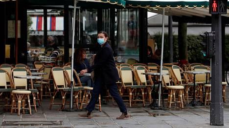 Kasvomaskia käyttänyt nainen käveli kahvilan ohitse Pariisissa 5. lokakuuta.