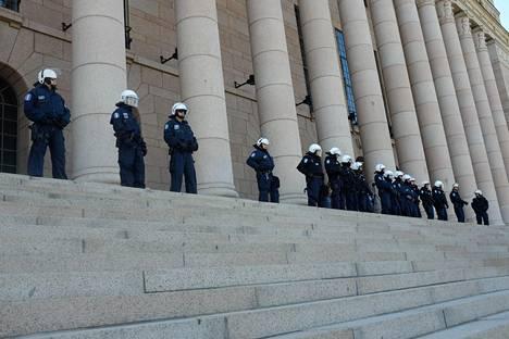 Poliisit seurasivat mielenosoitusta eduskuntatalon edustalla keväällä 2014.