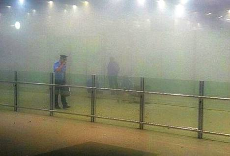 Poliisi tutki savun keskellä räjähdyspaikkaa Pekingin lentokentän 3-terminaalissa.