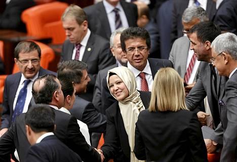 Puoluekollegat onnittelivat Turkin AK-puolueen kansanedustajaa Nurcan Dalbudakia hänen saavuttuaan parlamentin istuntoon huivi päässään Ankarassa torstaina.